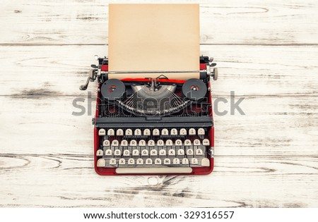 Old typewriter on wooden table. Antique object. Vintage style toned picture. German lettering - stock photo