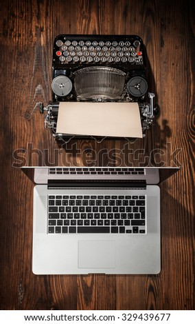 Old typewriter with laptop placed on wooden table. Concept of technology progress - stock photo