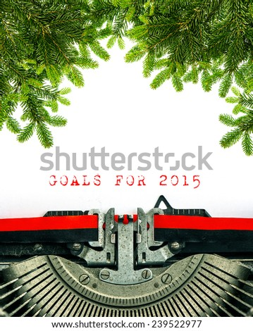 Old typewriter with sample text GOALS FOR 2015. Christmas tree twigs decoration. White grungy textured paper - stock photo
