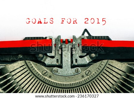 Old typewriter with sample text GOALS FOR 2015. Red words on white paper - stock photo