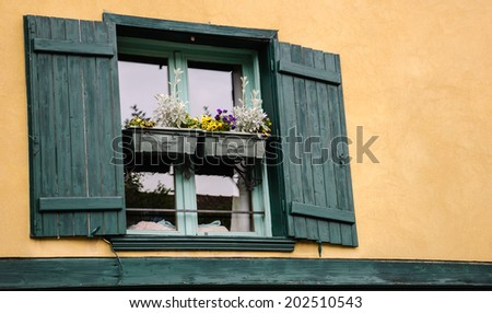 Old typical French house with ocher stucco wall, green wooden shutters and pansy  flowers on the window. (Amiens, Picardy, France)   - stock photo