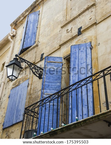 Old typical Mediterranean house with bright blue wooden shutters and stucco wall with peeling paint (Arles, Bouches-du-Rhone, Provence-Alpes-Cote d'Azur, France) - stock photo