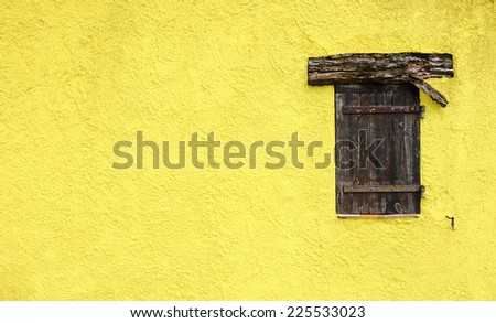 Old typical Mediterranean house with lemon stucco wall and closed wooden shutters. - stock photo
