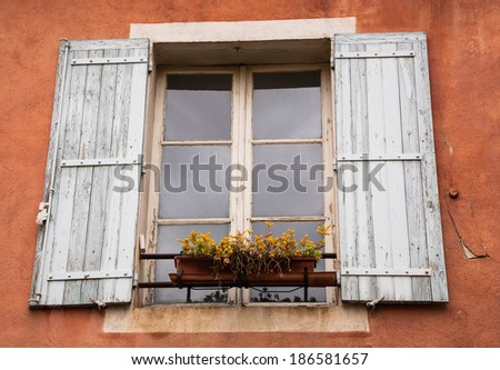 Old typical Mediterranean house with ocher stucco wall, wooden shutters and yellow flowers on the window (Arles, Bouches-du-Rhone, Provence-Alpes-Cote d'Azur, France) - stock photo