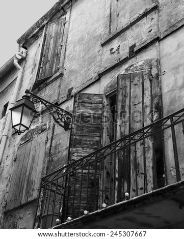 Old typical Mediterranean house with wooden shutters and stucco wall with peeling paint (Arles, Bouches-du-Rhone, Provence-Alpes-Cote d'Azur, France) Aged photo. Black and white. - stock photo