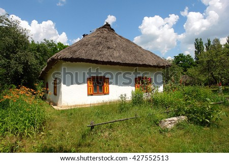 Old typical Ukrainian hut with a straw roof - stock photo