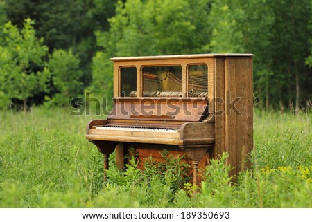 Old upright wood piano that has been abandoned in a green field / meadow / prairie. - stock photo