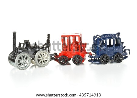 Old, used metal toy train with locomotive and wagons over white background - stock photo