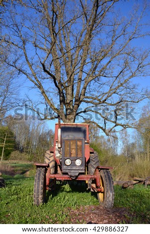 old used retro agriculture tractor in farm and big oak - stock photo