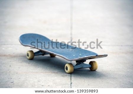 Old used skateboard isolated on the ground. Shallow depth of field. - stock photo