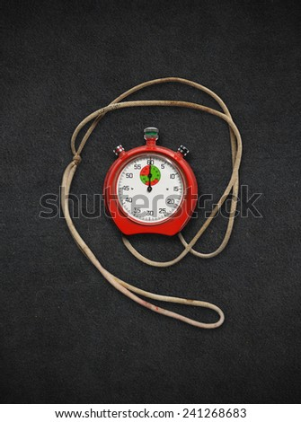 old used stopwatch on black fabric background - stock photo