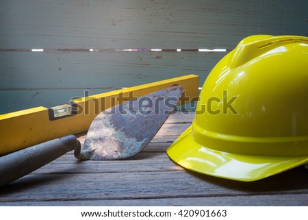 Old used trowel for masonry tools and yellow hard hat of worker - stock photo