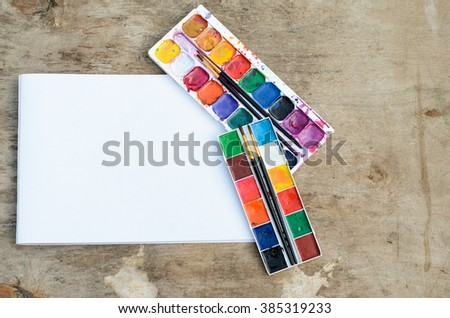 Old used watercolor paintbox and brushes, album pages with tools for drawing  - stock photo