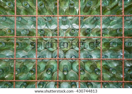 Old used wine bottles stacked in a shelf - stock photo