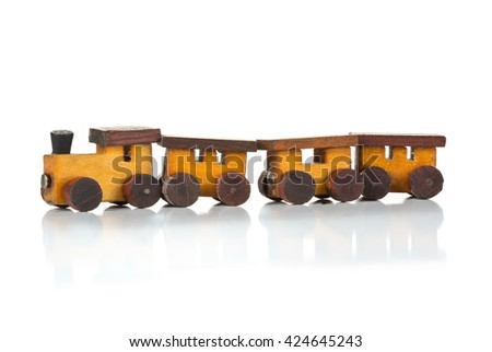 Old, used wooden toy train with locomotive and wagons over white background - stock photo