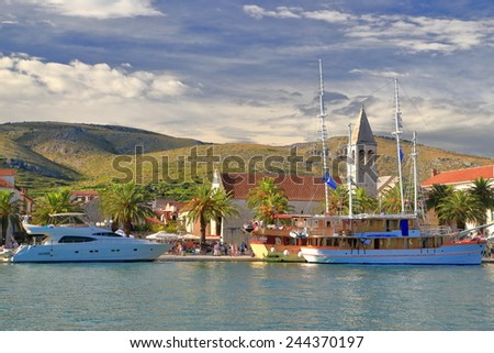 Old Venetian town by the Adriatic sea and leisure boats tied to the pier, Trogir, Croatia - stock photo