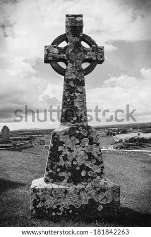 Old Victorian gravestone cross at Cashel cemetery in Ireland processed with black and white vintage filter. - stock photo