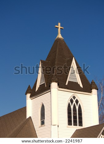 Old village church steeple with stained-glass windows and cross - stock photo
