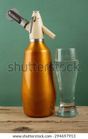 Old vintage aluminum  siphon and glass of water - stock photo