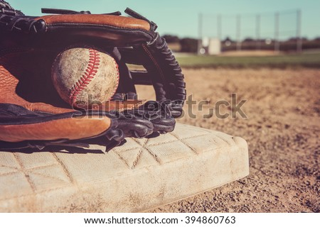 Old Vintage Baseball and glove resting on a base - stock photo