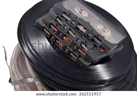 Old vintage bobbins, vinyl records and cassette tapes on a white  - stock photo