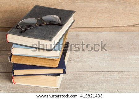 Old vintage books and glasses on a wooden table  - stock photo
