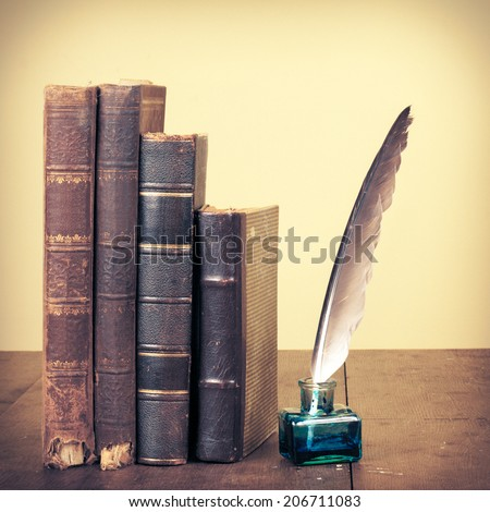 Old vintage books and ink quill pen on wooden desk. Retro style filtered photo - stock photo