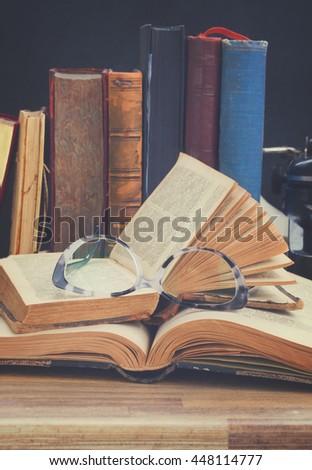 Old vintage books, glasses and typewriter - writting and publishing concept, retro toned - stock photo
