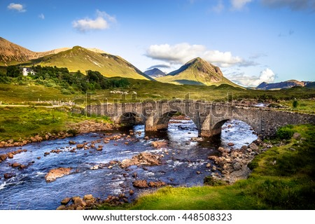 Old vintage brick bridge crossing river in Sligachan, Isle of Skye, Scotland with scottish landscape, vegetation, hills and mountains with fresh, blue water and sunny sky - stock photo