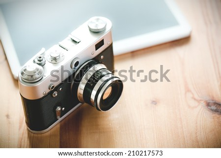 Old vintage camera with a tablet on a wooden table. - stock photo
