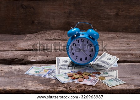 Old vintage clock on a money and coins. Time is money. Dollars and cents on a wooden background. - stock photo