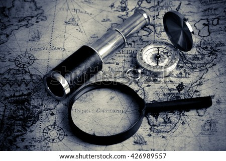 Old vintage compass ,telescope and magnifying glass on vintage map (Black and White tone) - stock photo