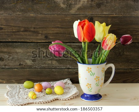 old vintage cup, tukips and easter eggs on wooden - stock photo