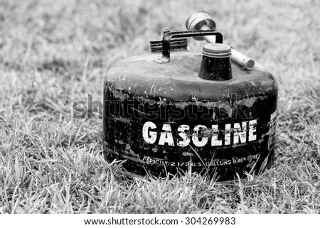 Old vintage gasoline can on grass background, black and white, shallow DOF - stock photo