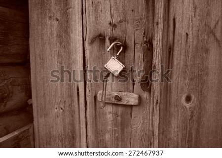 old vintage lock on a wooden door sepia - stock photo