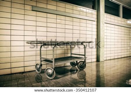 Old vintage metal stretcher in horror hospital - stock photo
