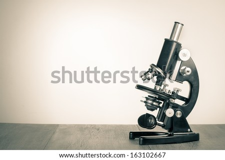Old vintage microscope on table for science background - stock photo