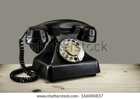 Old vintage phone with rotary disc on wooden table grunge backgr - stock photo