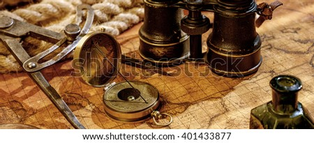 Old vintage retro compass and binoculars on ancient world map. Vintage still life. Travel geography navigation concept background. Vintage objects on the ancient world map. - stock photo