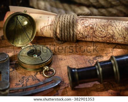 Old vintage retro compass, measuring devices and magnifying glass on ancient world map. Vintage still life. Travel geography navigation concept background. - stock photo