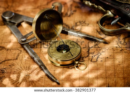Old vintage retro compass, measuring devices and vintage gun on ancient world map. Vintage still life. Travel geography navigation concept background. - stock photo