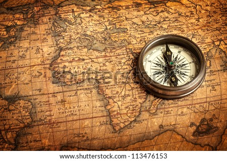 Old vintage retro compass on ancient map.The map used for background is in Public domain. Map source: Library of Congress. Country: Belgium Year: 1570. Author: Abraham Ortelius (1527-1598) - stock photo