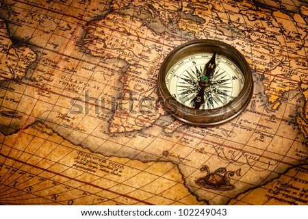 Old vintage retro compass on ancient map. The map used is in Public domain. Map source: Library of Congress. Country: Belgium Year: 1570. Author: Abraham Ortelius (1527-1598) - stock photo