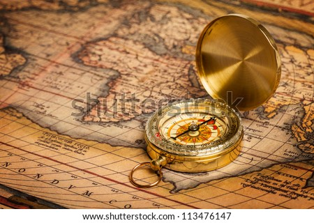Old vintage retro golden compass on ancient map. The map used for background is in Public domain. Map source: Library of Congress. Country: Belgium Year: 1570. Author: Abraham Ortelius (1527-1598) - stock photo