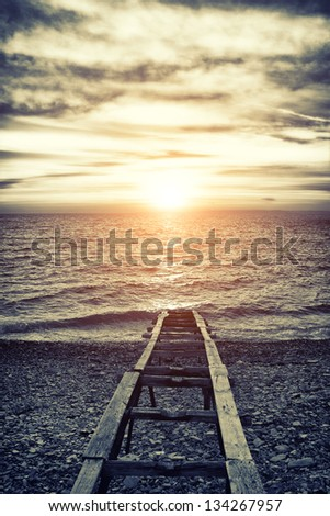 Old vintage sea wharf during sunset - stock photo