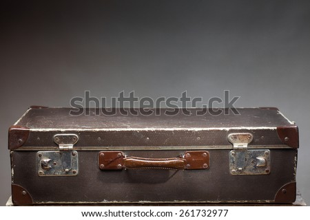 Old vintage suitcase on wooden table on blank gray background - stock photo