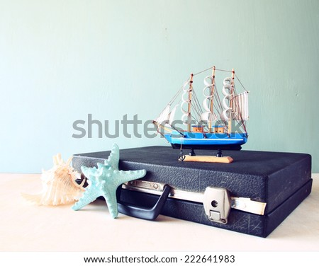 Old Vintage sutcase with toy boat' starfish and seashell  on wooden board. travel and voyage concept. retro filtered image - stock photo