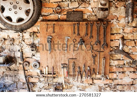 Old vintage tools hanging on a wooden clipboard, grunge background. - stock photo