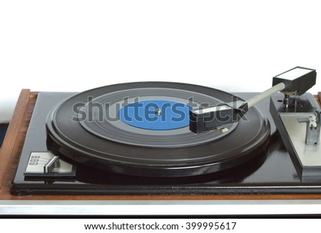 Old vintage turntable in wooden case with rotation vinyl record with blue label isolated on white background. Horizontal photo front view closeup - stock photo