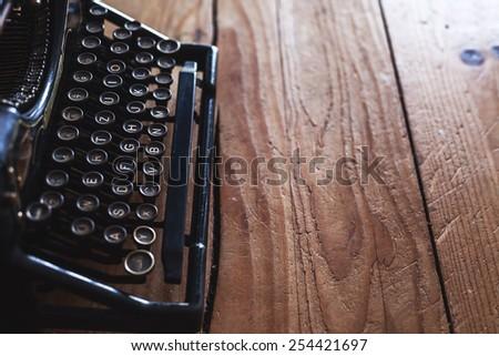 Old vintage typewriter on wooden table, beside window.  - stock photo